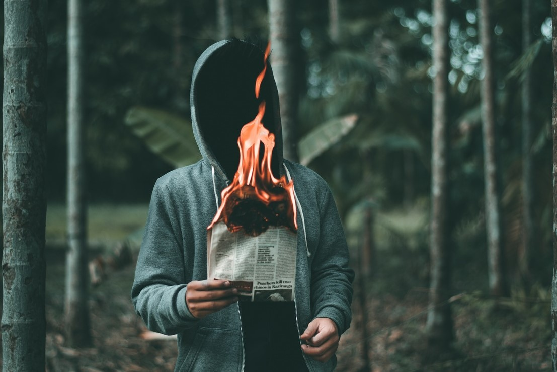 The shame game, man holding burning newspaper